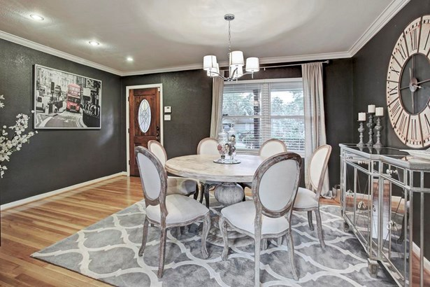 Upon entry, guests are welcomed into the foyer area with the dining room designated by a stylish chandelier. Large picture windows with blinds look out over the front patio and tree lined streets. (photo 4)