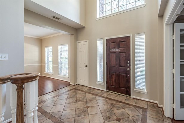 Tall 2-story tiled entry with coat closet and huge upper arched window opens to formal dining on left and the formal study through double doors on the right. (photo 3)