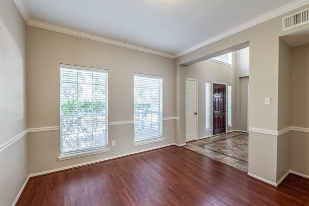 Elegant formal dining room with accented chair railing and molding is just off the entry through large opening and also adjacent to the kitchen for easy entertaining. (photo 4)