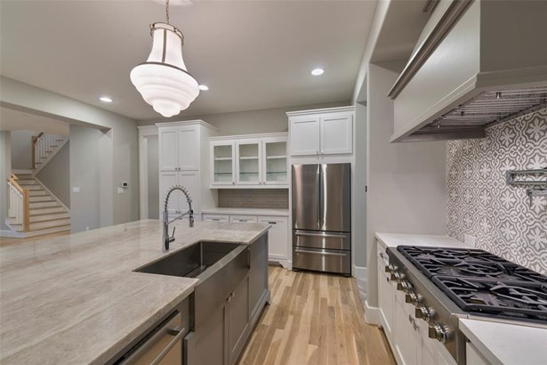 Beautiful kitchen features white custom built cabinetry and oversized quartzite island. Also features cement tile back splash, pot filler, thermador cook top, glass cabinetry and designer lighting. (photo 4)