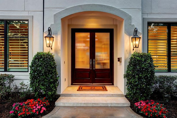 The welcome mat is out on the tiled front porch, featuring lantern lighting and majestic double wood entry doors with ribbed, opaque glass inserts. The arched entry adds architectural interest to the inviting front porch. (photo 2)