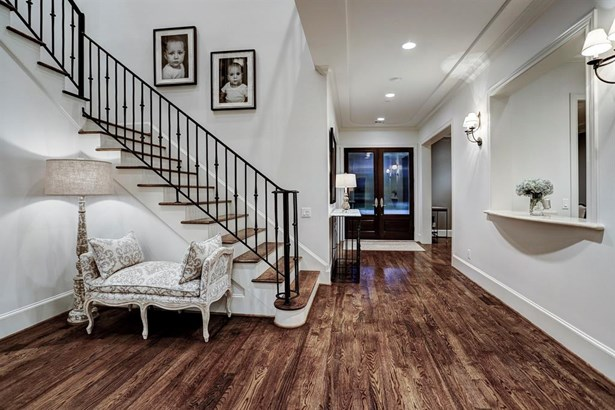 On display here is the lovely staircase with iron spindles and wood steps as it ascends from the Foyer to the second floor. Rich wood flooring is found throughout all areas with the exception of baths and laundry rooms. (photo 4)