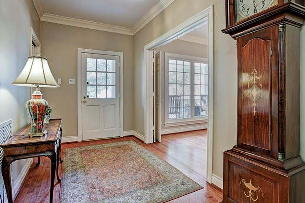 Front door opens into large foyer with its high ceilings, crown molding and wood flooring. (photo 3)