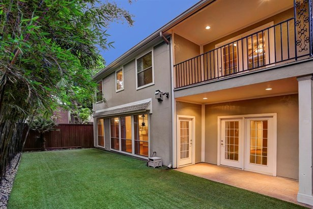Easily maintained turf backyard with covered porch and balcony. Stalk bamboo added including outdoor lighting and mosquito system. (photo 3)