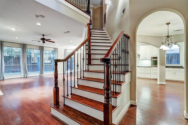 A beautiful wood and wrought iron staircase is a focal point in the entry. It operates as a separation of the dining a living spaces. (photo 4)