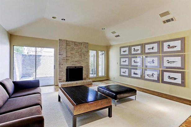 The very generous foyer opens into this spacious and comfortable great room living area with raised coffered ceilings, privacy to the streetside, wood flooring, and this charming fireplace flanked by windows on one side and glass patio doors on the other (photo 4)