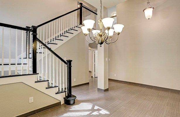 Aesthetically pleasing with its soft gray walls this hard wood staircase with white spindles adds so much charm to this great home. (photo 3)