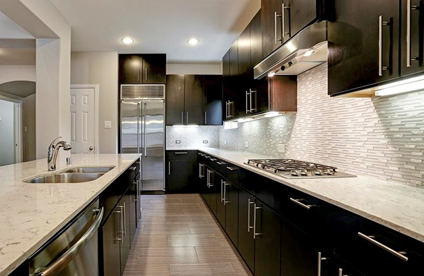 """The built in refrigerator, sleek cabinets, fabulous backsplash, and stunning counters add tremendous """"WOW"""" factor to this chef's kitchen. (photo 5)"""