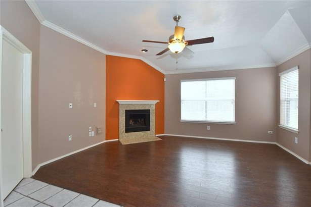 Nice, spacious living room with a gas fireplace, lots of big windows, crown molding and a lighted ceiling fan. (photo 5)