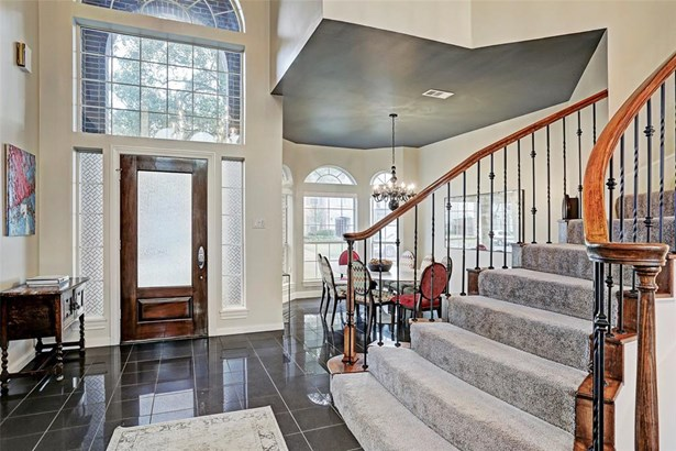 The dramatic staircase and living room with a two story tall ceiling greets you as soon as you enter this charming home. (photo 3)