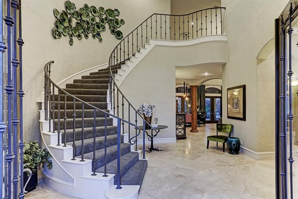 Upon entrance is the carpeted spiral staircase and a glimpse of extended living room area. Exquisite Traventine stone flooring from Brazil is found throughout the downstairs. (photo 2)