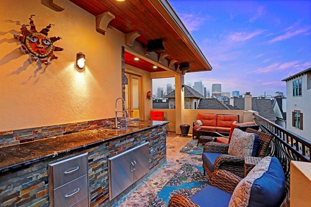 Incredible downtown views from the rooftop deck. This outdoor living space is complete and ready for full enjoyment. Surround sound speakers, television, stainless steel beverage cooler, sink, leathered-granite counters, sconce lighting, and two separate (photo 2)