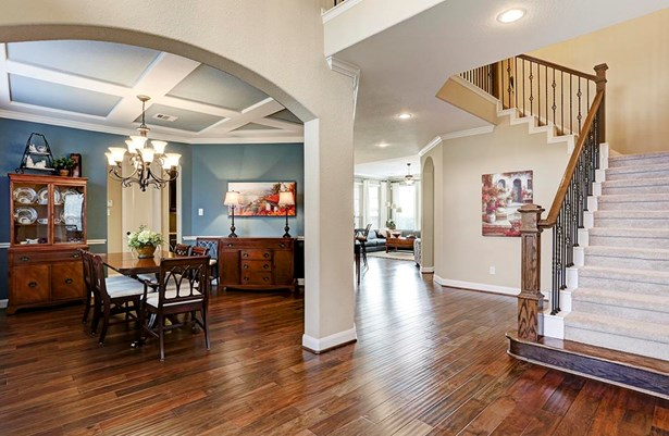 Open entry with hardwood floors with view to dining room and staircase with wood step and wrought iron spindles. (photo 2)