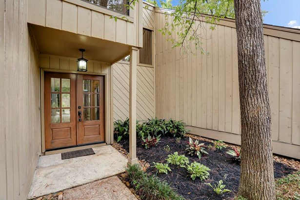The entranceway contains beautiful wooden French doors and lovely landscaping. (photo 2)
