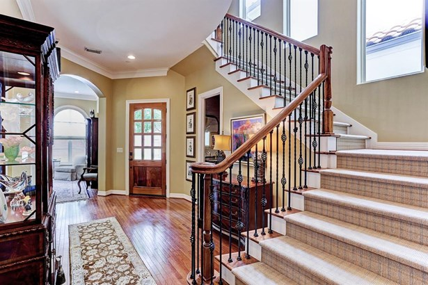 The light filled entry welcomes you to an elegant foyer with wrought iron railing staircase, hardwoodfloors, and formal living room... (photo 3)