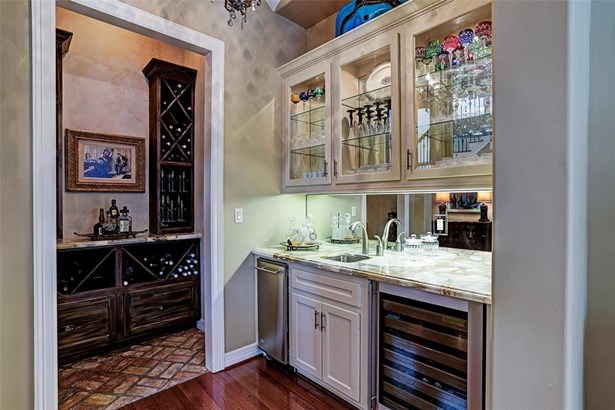 The redesigned bar has custom granite, glass front cabinets, glass shelving, beverage refrigerator, ice makerand extra storage below..The adjacent wine/grotto area (which was predesigned as the elevator shaft) is perfect for entertaining with wine storag (photo 5)