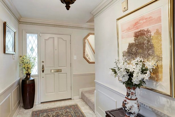 One steps into this gracious entry hall with dentil style double crown molding and lovely wainscot paneling. (photo 3)