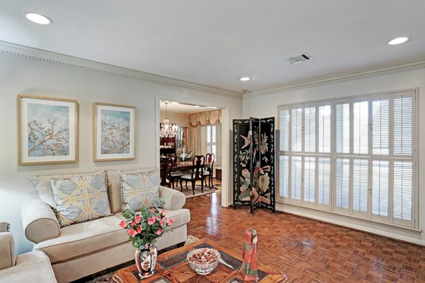 From the welcoming foyer, one may enter the formal living room. Note the warm parquet hardwood floors, lovely dentil style crown moldings, recessed lighting & neutral colors. The large front windows are shuttered but bring in lots of natural light. (photo 4)