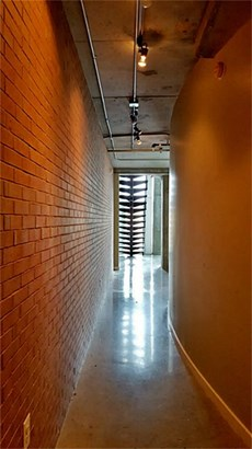 From the entry, the exposed brick wall nicely compliments the polished concrete flooring. (photo 4)