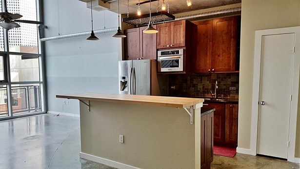 Breakfast bar kitchen with pendent lighting & stone back splash. (photo 5)