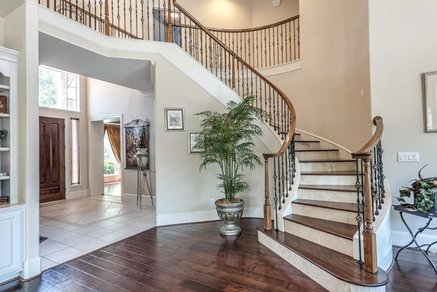 Great view of the graceful winding staircase just off the entry which opens to the large open den. (photo 3)