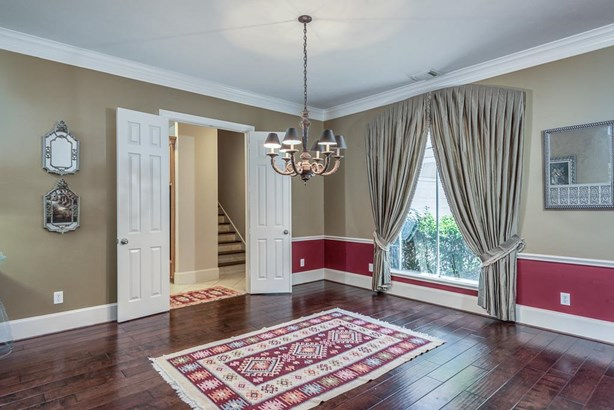 Elegant formal dining room has crown molding, wood floors & nice outdoor views of the front lawn. The double doors open to the kitchen & back stairway. This is the garage entry point & also very large utility room complete with sink & great storage. (photo 5)