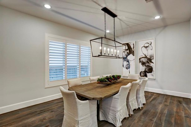 The dining room has a beautiful aged iron linear pendant chandelier and is open to the entrance. The butlers pantry leading to the kitchen is to the right. (photo 4)