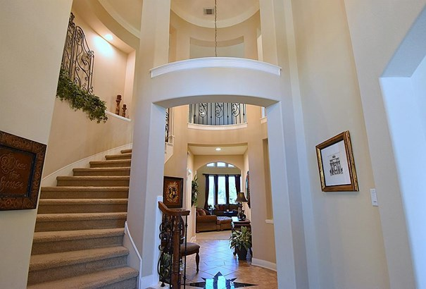 Grand 2-Story Rotunda Ceiling and Granite Inlay in the Floor Below as you approach the Entry vestibule and Gallery on the way to the Family Room. One of Two Staircases - Chandelier. Powder Room to the left. (photo 5)