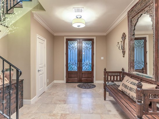 Travertine entry with 9-ft. ceilings, crown molding and stairway to the 2nd floor. The other end of the entry hall leads to an amazing executive study. (photo 3)