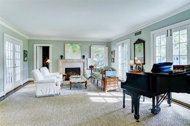 The formal living room has light streaming in on three sides. The front French door to the front yard and the French doors on the left lead to the pool and backyard. The fireplace has gas logs but is also a woodturning chimney. Behind the fireplace is a q (photo 4)