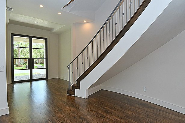 Inviting Entry with dramatic curved staircase with white oak stained risers and treads. High end smooth finish plaster at stairway, entry, vaulted ceiling and fireplaces. (photo 3)