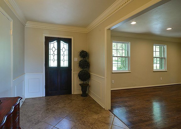 Tiled foyer has a large closet, crown molding, and wainscoting. (photo 5)