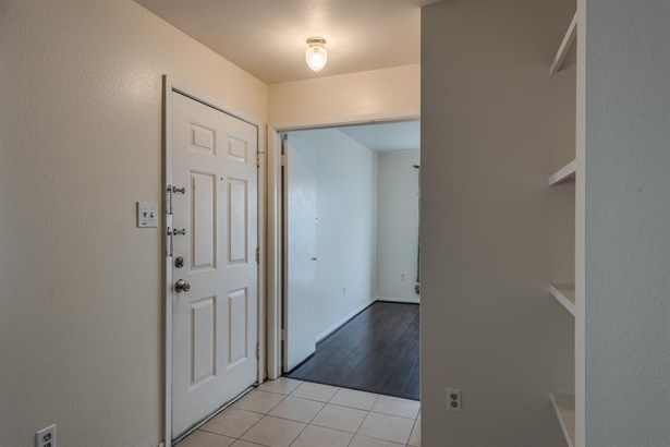 Tiled entry from the private balcony opens into the living area in foreground and 2nd bedroom through double doors across the entry. (photo 3)