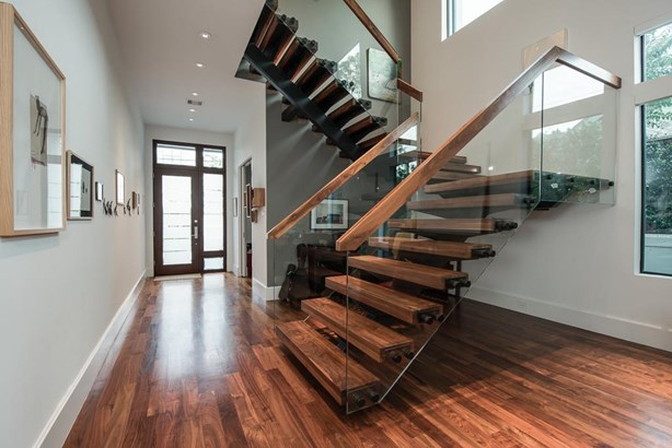 Beautiful walnut wood flooring with warm tones and fantastic incoming natural light envelope this contemporary home. Door opening on the right is the study. (photo 3)