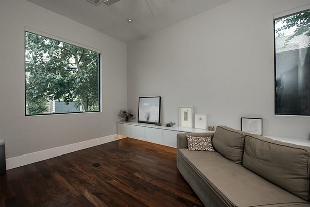 Double doors open to a light-filled study with lower built-in storage, ceiling fan and recessed lighting above. (photo 4)