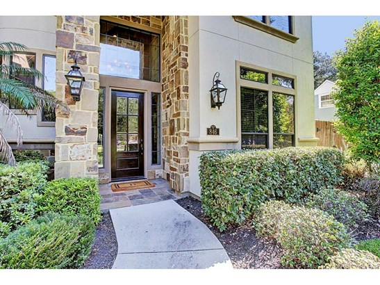 The inviting entry is beautifully accented by gas lanterns and attractive stone against the stucco. (photo 3)