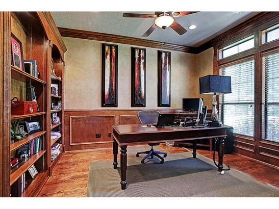 To the right of the entry is the home office with french doors, stained trim work, lit built-ins, and views of the lush front yard. (photo 5)