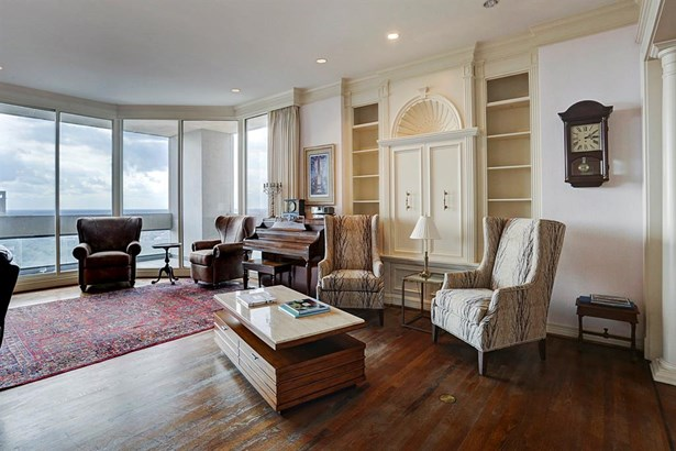 The other half of the living area can be used for a den/TV room. Close the custom drapes for privacy or take advantage of the natural light that pours in the floor to ceiling windows. The lovely arched glass doors lead to a formal study/office. (photo 3)