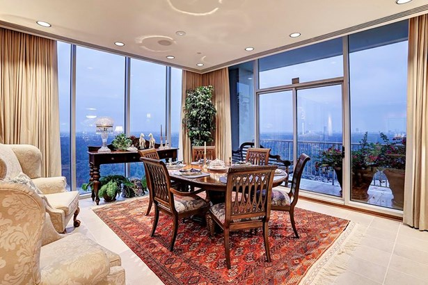 Adjacent to the dining room, at the end of the great room, is a large balcony with views of Memorial Park and downtown Houston (photo 4)