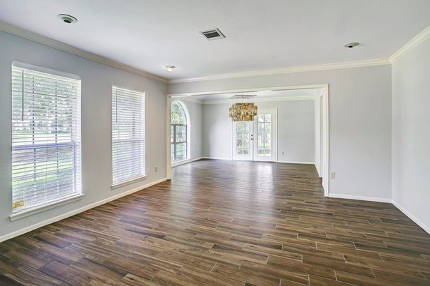 Many updates throughout, neutral interior paint color (2017), Wood plank porcelain tile floors throughout most of house, crown molding, window coverings, and great windows. Open living room (15x13) and dining room (15x13). (photo 3)
