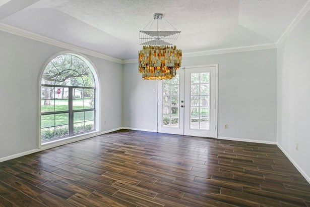 Closer view of dining room and fun decorative chandelier. French doors to side patio, arched window overlooks north view of home. (photo 4)