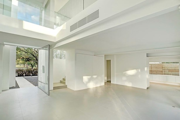 A large custom pivoting glass door creates a sense of arrival into what promises to be an extraordinary space. (photo 3)
