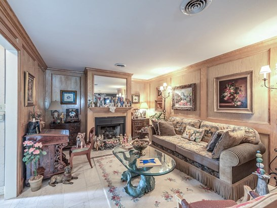 Paneled living room with fireplace and marble tile floors provide a cozy setting for entertaining. (photo 5)