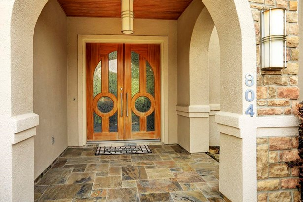 A covered slate tile front porch leads to an ornate double door. (photo 3)