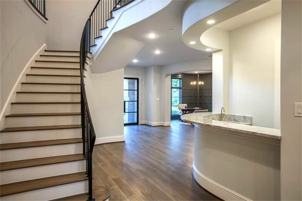 The entrance is perfectly designed. The bar and butler s pantry to the right feature a custom wine holder, sink, wine chiller, ice machine and quartzite counters. (photo 2)