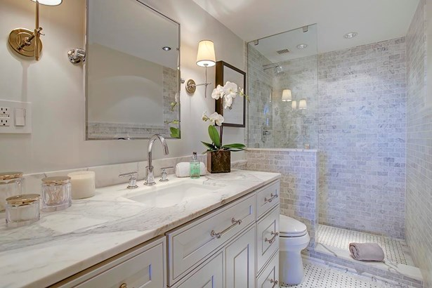 The master bath has a large shower with Carrara honed marble and frameless glass wall,.heated basket weave marble floor,halo recessed halogen lights and custom vanity with white statuary marble countertop. (photo 2)