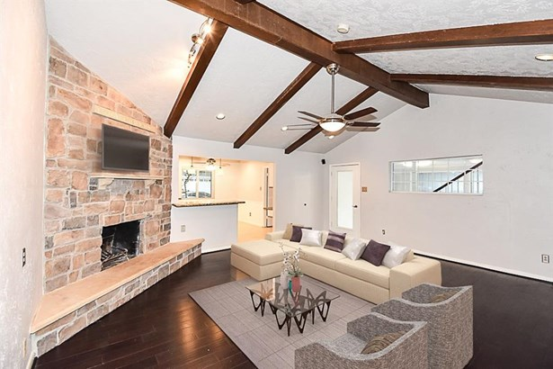 Inviting family room with bamboo floors, wood beams and cozy stone fireplace. (photo 3)