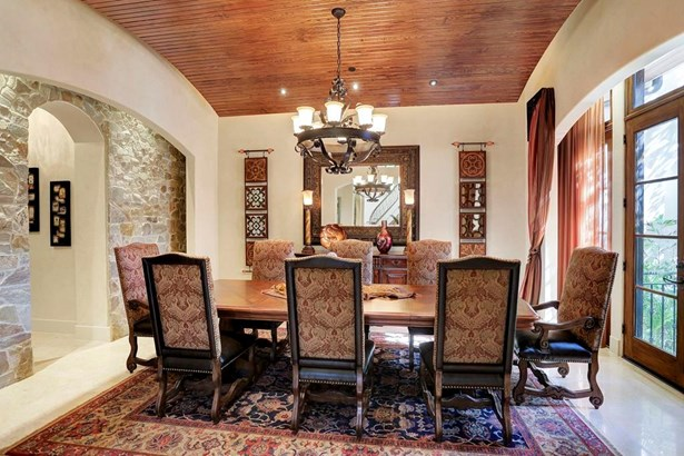 Formal Dining room features a barrel floating ceiling with cove lighting, custom wrought iron chandelier and Jerusalem limestone floors. The double French doors lead to a private courtyard with an outdoor fireplace. (photo 4)