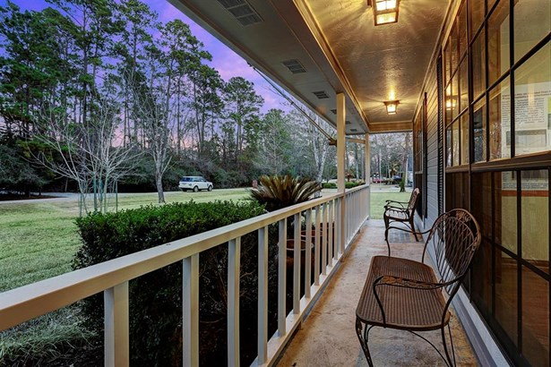 Long and lengthy covered porch which overlooks the wooded neighboring lot in front of the home. (photo 3)