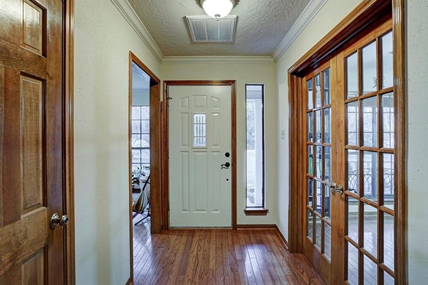 Wooden floors and doors welcome guests into the home. Upon entrance is the office and formal dining room. (photo 4)